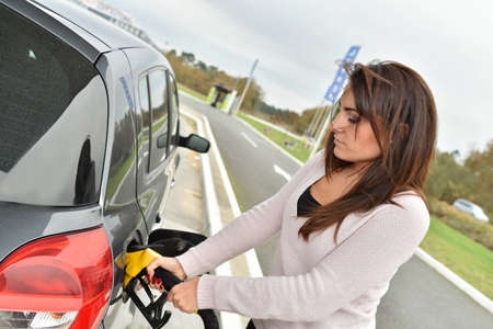 Young woman filling her car tank at gas station Foto de archivo