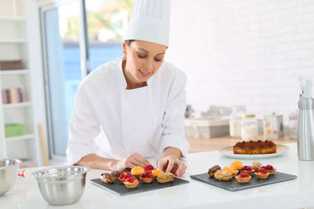 chef kitchen: Pastry-cook preparing plate of cake bites