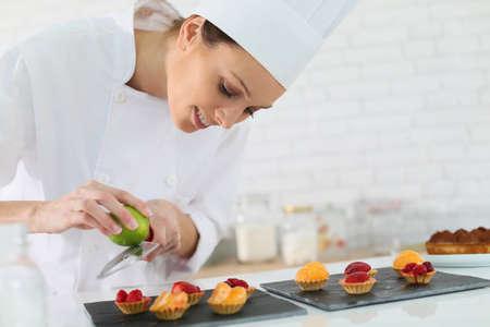 pasteles: Pastelero shreding ralladura de lim�n sobre las picaduras de la torta Foto de archivo