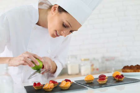 pastry: Pastry-cook shreding lemon zest over cake bites Stock Photo