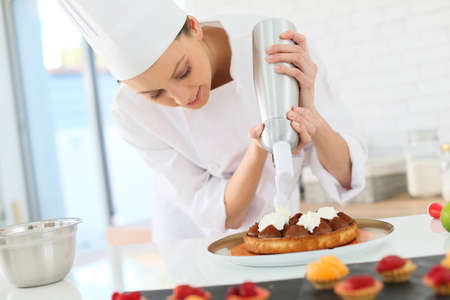 cook: Pastry cook spreading whipped cream on tart