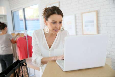 shop tender: Beautiful shopgirl working in clothing store