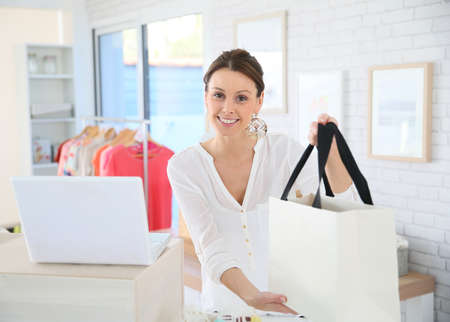 Seller in clothing store giving bag to customer Stock Photo