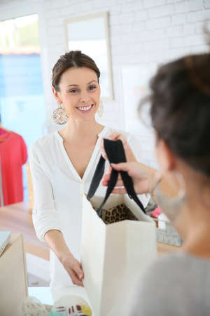 shop tender: Seller in clothing store giving bag to customer Stock Photo