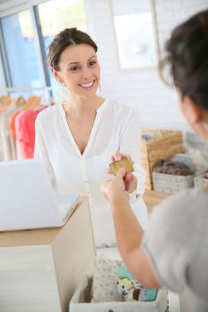 shop tender: Customer in clothing store giving credit card to saleswoman