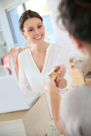 shopgirl: Customer in clothing store giving credit card to seller Stock Photo