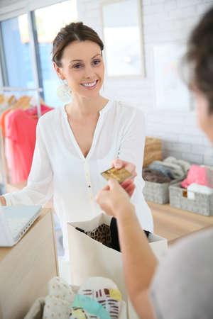 maquina registradora: Cliente en almacén de ropa que da la tarjeta de crédito al vendedor