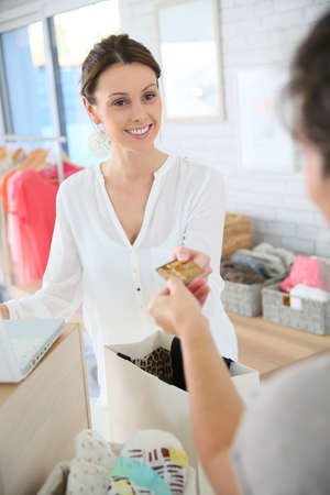 shop tender: Customer in clothing store giving credit card to seller Stock Photo