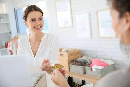 tienda de ropas: Cliente en almac�n de ropa que da la tarjeta de cr�dito al vendedor