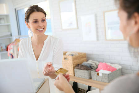 Customer in clothing store giving credit card to seller Stock Photo