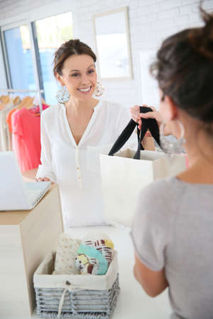 shop tender: Seller woman in store giving purchase bag to client