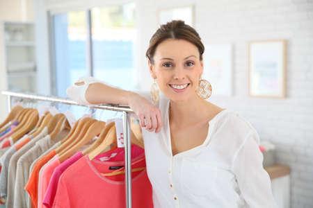 vendedor: Tienda mujer de pie junto a la ropa en almacén