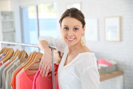 shop tender: Shop woman standing by clothes in store