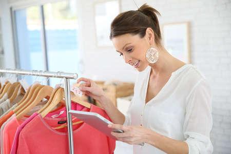 shop tender: Shop woman preparing summer sales in store