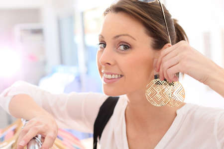 trying on: Shopping girl trying earings on in store