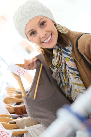 choosing clothes: Beautiful woman in store choosing clothes on sale Stock Photo