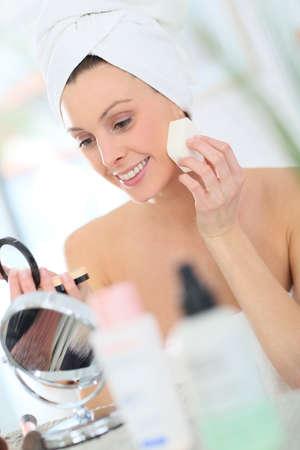bathroom women: Beautiful woman putting makeup on