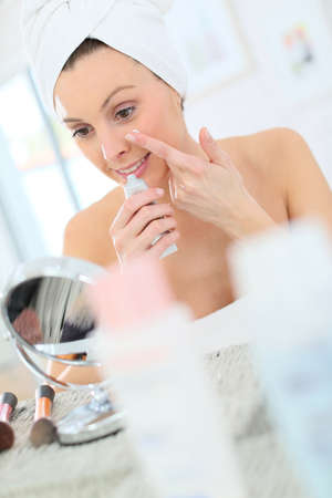 beautycare: Beautiful woman applying moisturizing cream on her face Stock Photo