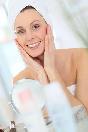 woman face cream: Beautiful woman applying moisturizing cream on her face Stock Photo