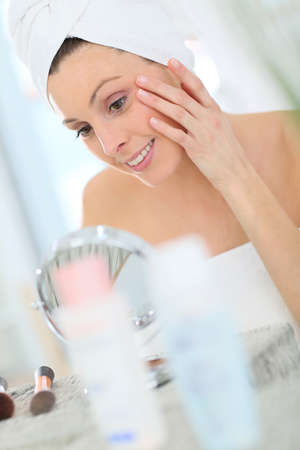 antiaging: Beautiful woman applying moisturizing cream on her face Stock Photo