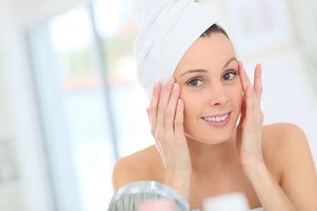 Beautiful woman applying moisturizing cream on her face Stock Photo