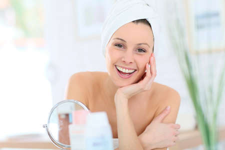 beautycare: Cheerful woman in bathroom with towel over hair Stock Photo
