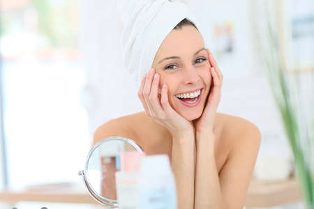 bathroom mirror: Cheerful woman in bathroom with towel over hair Stock Photo
