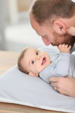 diaper changing table: Daddy cuddling baby boy on changing table