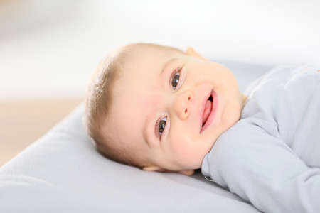 diaper changing table: Portrait of smiling baby boy laying on changing table Stock Photo
