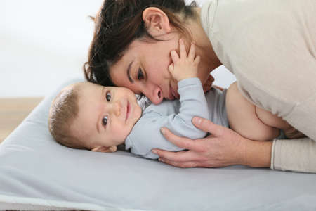 diaper changing table: Mommy cuddling baby boy on changing table