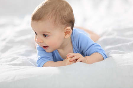cute baby: 8-month-old baby boy laying on bed