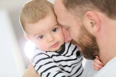 Portrait of daddy embracing baby boy photo