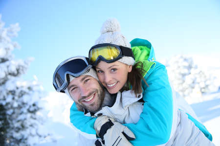 Man giving piggyback ride to girlfriend in snowy mountain photo