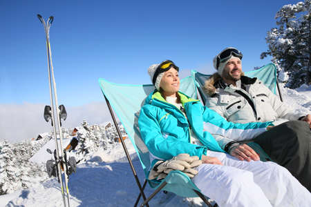 Couple of skiers sunbathing in long chairs photo