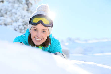 laying down: Cheerful girl in ski outfit laying down in snow Stock Photo
