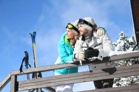 log cabin in snow: Couple of skiers admiring panorama from log cabin Stock Photo
