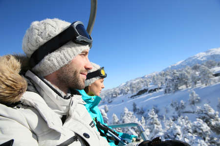 chairlift: Couple of skiers going up ski slope with chairlift