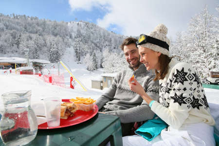 skiers: Couple of skiers having a snack on skiing day Stock Photo