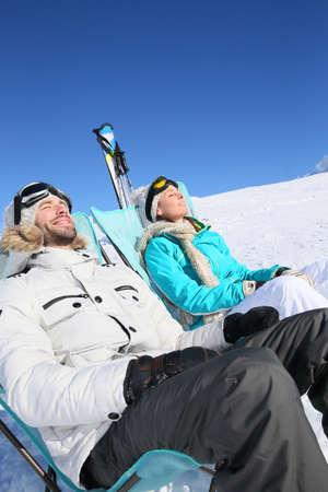 Couple of skiers sunbathing at top of ski slope photo