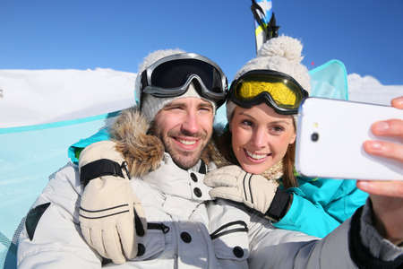 selfy: Couple of skiers making selfy with smartphone