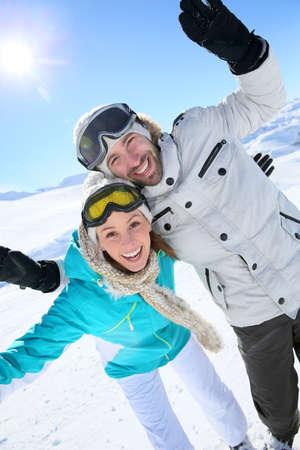 Cheerful couple having fun at top of ski slope photo