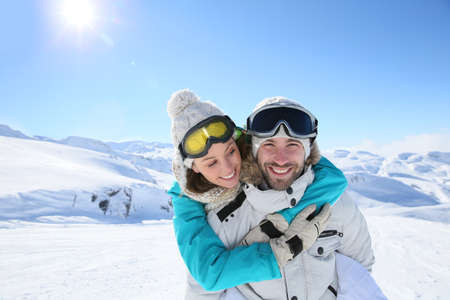 Man holding girlfriend on his back at the top of mountain photo