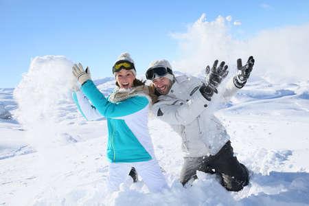 snowballs: Coppia in montagna nevosa fare palle di neve lotta
