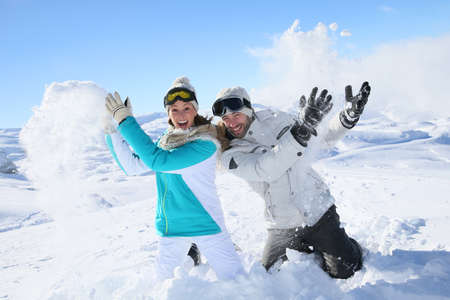 snowballs: Couple in snowy mountain doing snowballs fight