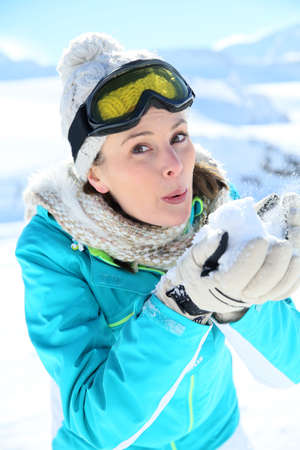 Portrait of skier blowing snow flakes photo