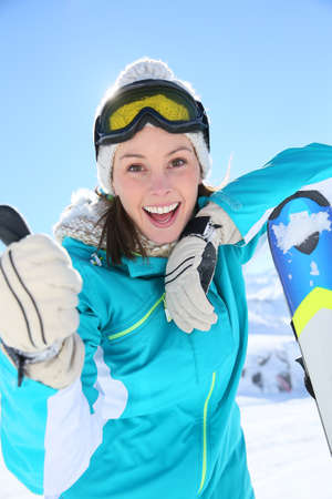 Woman in ski outfit standing at top of mountain photo