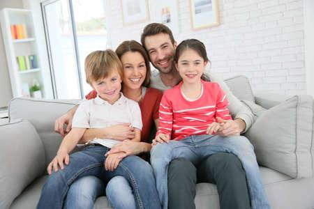 personas sentadas: Familia alegre en casa sentado en el sof�