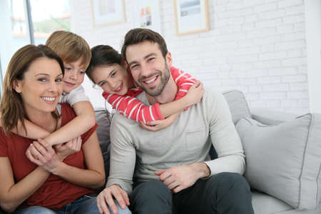abrazar familia: Familia alegre en casa sentado en el sof�