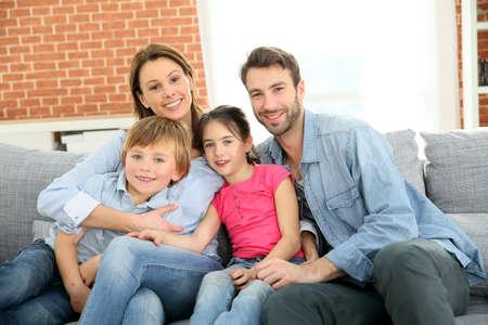 niños sentados: Familia alegre en casa sentado en el sofá