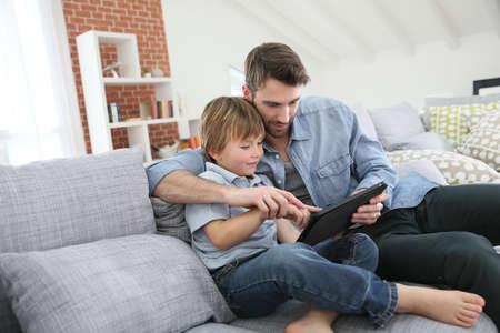zábava: Otec s malým chlapcem pomocí digitální tablet doma Reklamní fotografie